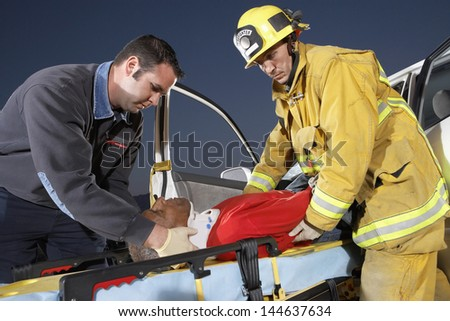 Side view of a fire fighter and paramedic assisting man at crash site - stock photo
