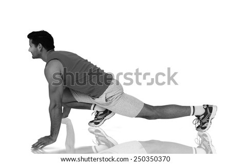 Side view of a fit man doing stretching exercise against mirror