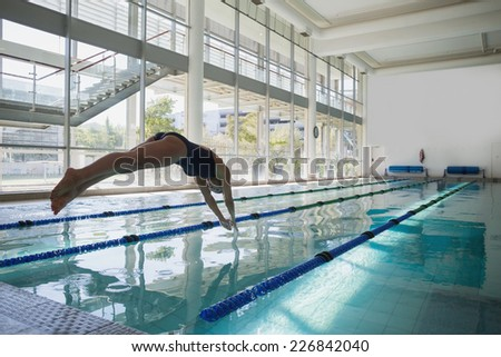 Side view of a fit swimmer diving into the pool at leisure center - stock photo