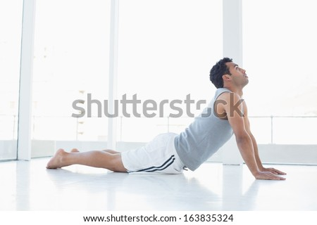 Side view of a fit young man doing the cobra pose in a bright fitness studio - stock photo