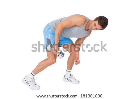 Side view of a fit young man exercising with dumbbell over white background