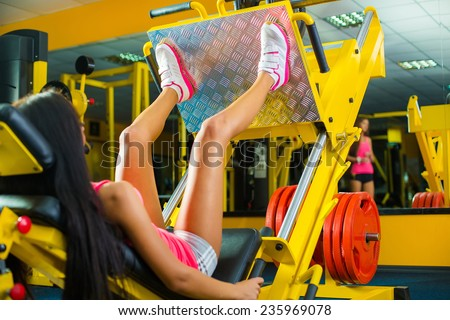 Side view of a fit young woman doing leg presses in the gym - stock photo