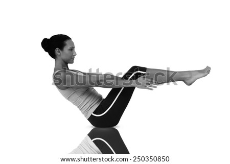 Side view of a fit young woman doing the boat pose against mirror - stock photo