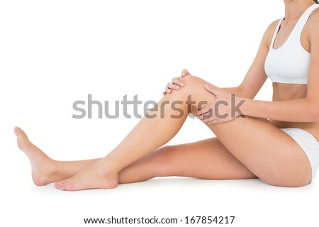 Side view of a fit young woman with knee pain sitting over white background