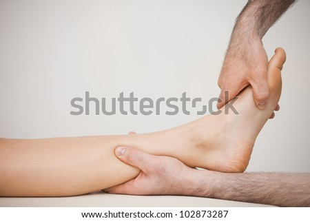Side view of a foot being massaged in a medical room