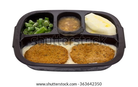 Side view of a frozen fried chicken patties TV dinner with potatoes, green beans and apples in sauce on a white background. - stock photo