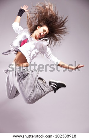 side view of a full of energy woman dancer screaming and making a difficult jump