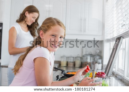 Side view of a girl helping mother to prepare food in the kitchen at home