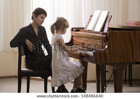 Side view of a girl playing piano accompanied by teacher