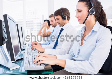 Side view of a group of business colleagues with headsets using computers at office desk