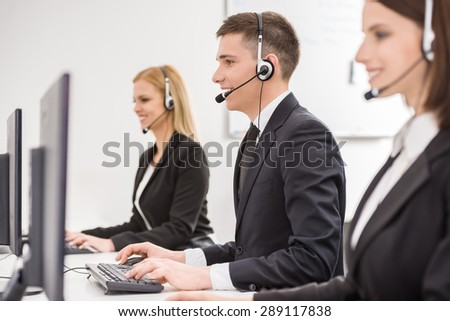 Side view of a group of business colleagues with headsets using computers at office desk. - stock photo