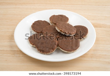 Side view of a group of organic rice cookies with milk chocolate icing on a wood table top. - stock photo