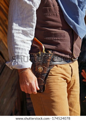 Side view of a gunfighter ready to draw his gun - stock photo