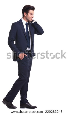 Side view of a handsome business man walking while holding one hand in his pocket and the other one to his neck - stock photo