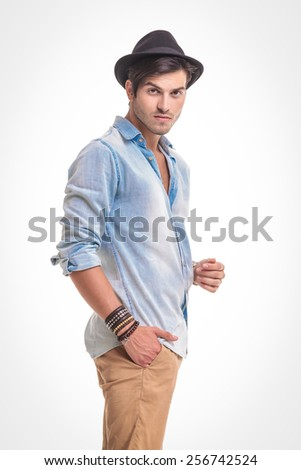Side view of a handsome casual man looking at the camera while holding one hand in his pocket. - stock photo
