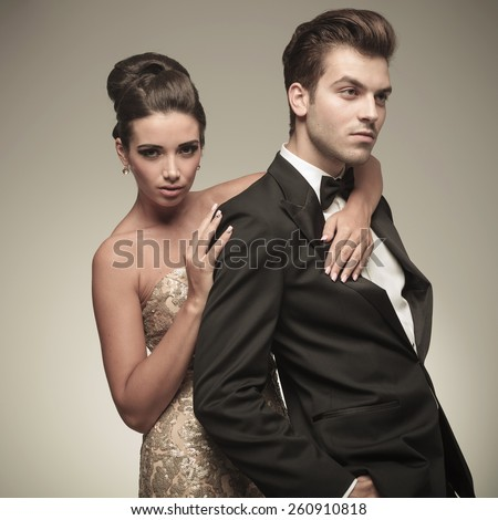 Side view of a handsome elegant man looking away while his wife is embracing him. - stock photo