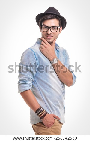 Side view of a handsome fashion man holding one hand in his pocket while fixing hs beard. - stock photo