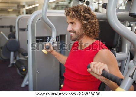 Side view of a handsome smiling young man working on fitness machine at the gym - stock photo