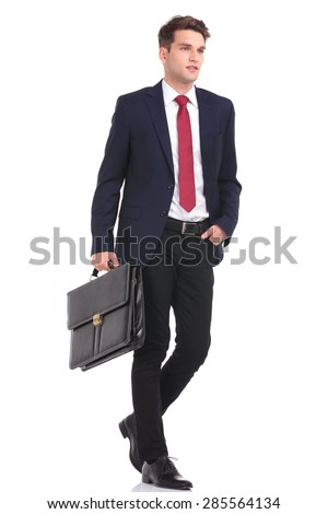 Side view of a handsome young business man walking with his hand in pocket while holding a briefcase. - stock photo