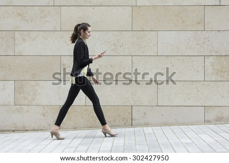 Side view of a happy Caucasian Businesswoman walking on city street using a smart phone.