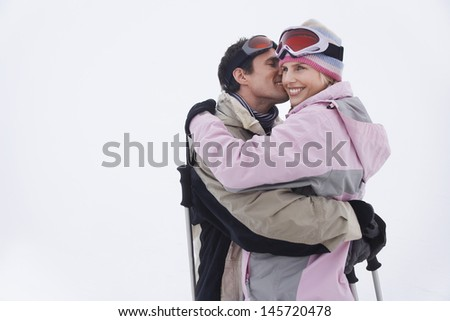 Side view of a happy couple in warm clothing embracing in snow - stock photo
