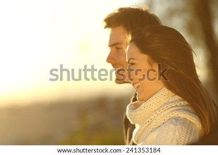 Side view of a happy couple looking at sunset in winter on the beach - stock photo