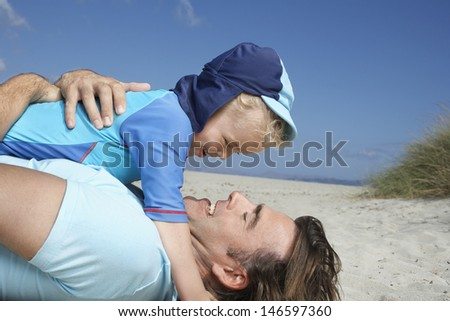 Side view of a happy father playing with young son at the beach - stock photo