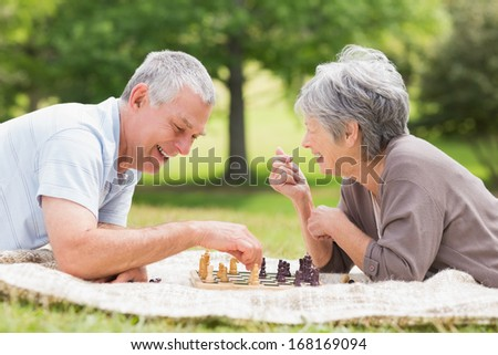 Side view of a happy senior couple playing chess at the park - stock photo