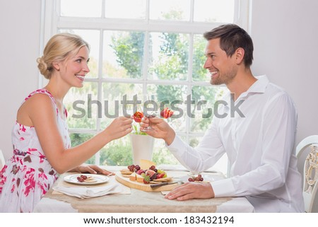 Side view of a happy young couple toasting wine glasses over food at home - stock photo