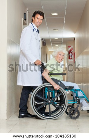 Side view of a happy young doctor assisting senior woman sitting in a wheel chair - stock photo