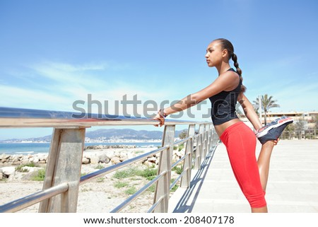 Side view of a healthy african american woman with perfect body stretching her legs, exercising and training against a blue sea and sky during a sunny day on a sandy beach. Sport lifestyle outdoors. - stock photo