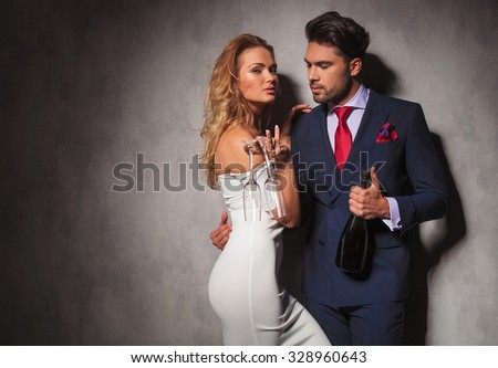 side view of a hot couple holding a bottle of champagne , man is looking at his woman while she is holding two glasses