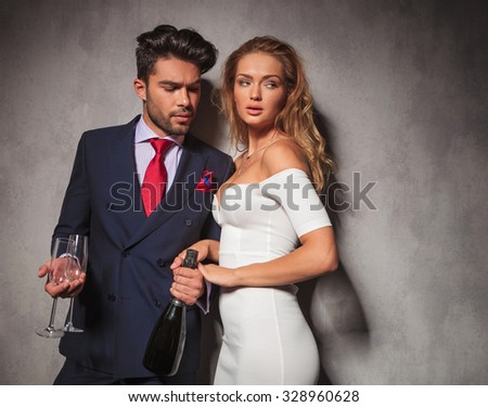 side view of a hot fashion couple with champagne and glasses ready to celebrate - stock photo