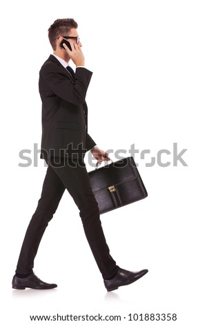 side view of a hurrying business man talking on the mobile phone on white background - stock photo
