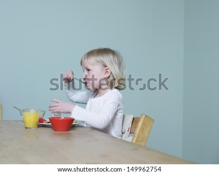 Side view of a little blond girl eating breakfast at dining table - stock photo