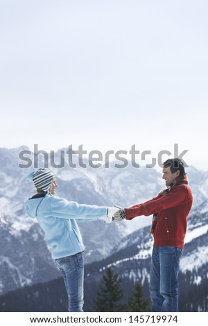 Side view of a loving couple holding hands against snow covered mountain - stock photo