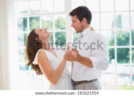 Side view of a loving young couple dancing at home - stock photo