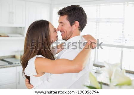 Side view of a loving young couple embracing in the kitchen at home - stock photo