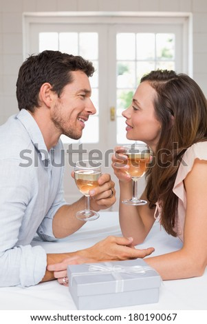 Side view of a loving young couple with wine glasses looking at each other