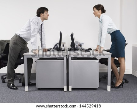 Side view of a male and female rival business colleagues in office - stock photo