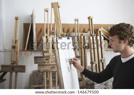 Side view of a male artist drawing charcoal portrait in studio - stock photo