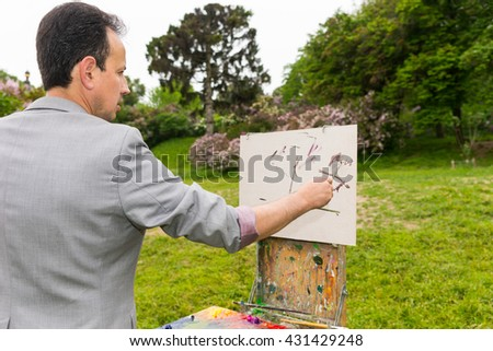 Side view of a male artist during creation a sketch on a trestle and easel painting with oils and acrylics in a forest - stock photo