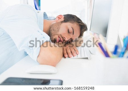 Side view of a male artist with head resting on keyboard in the office