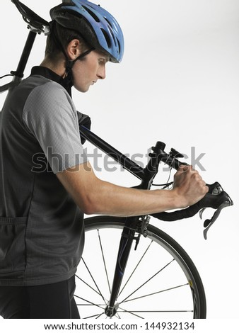 Side view of a male bicyclist carrying bicycle against white background - stock photo