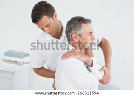 Side view of a male chiropractor examining mature man at office - stock photo