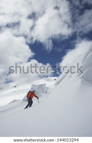 Side view of a male hiker going up snowy mountain slope against clouds - stock photo