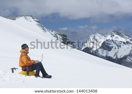 Side view of a male hiker using laptop on snowy mountain slope - stock photo