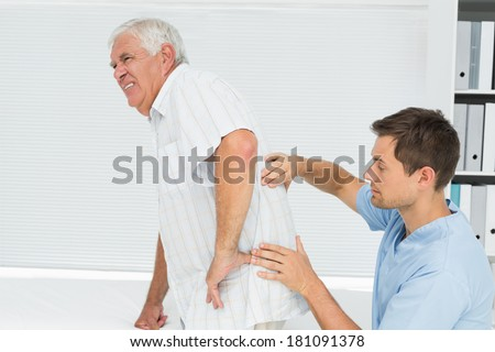 Side view of a male physiotherapist examining senior mans back in the medical office - stock photo