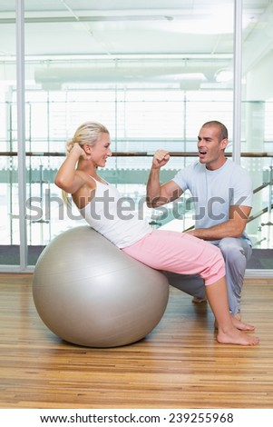 Side view of a male trainer assisting woman with abdominal crunches at the gym - stock photo