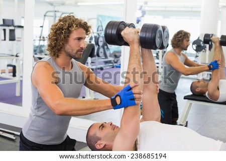 Side view of a male trainer assisting young man with dumbbells in the gym - stock photo
